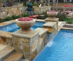 Remodeled Swimming Pool in Plano with stone steps and decking as well as a waterfall from the spa to the pool